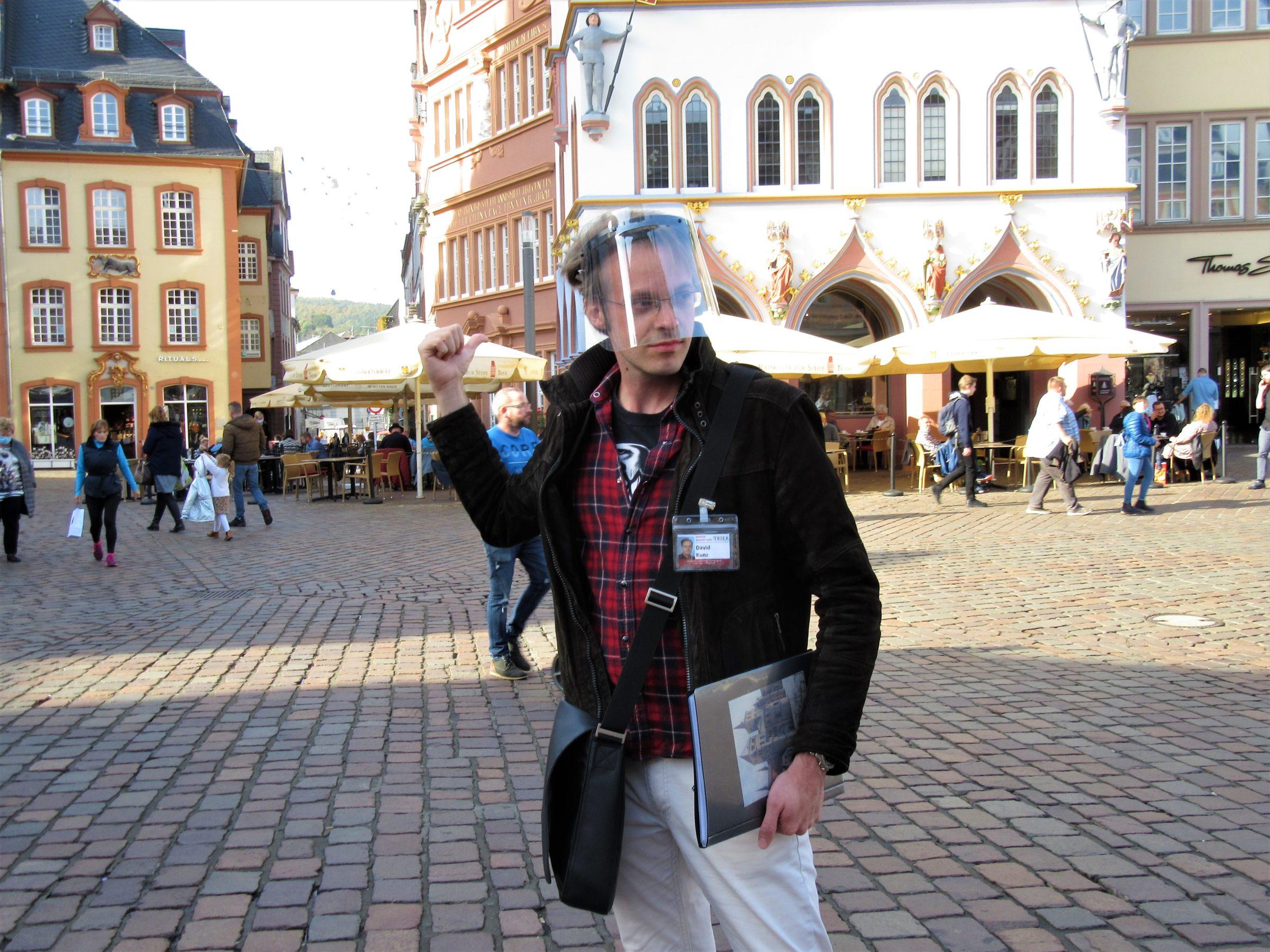 Gästeführer David Kunz erzählt bei einer Stadtführung über den Wiederaufbau der Steipe, sein Lieblingsbauwerk in Trier.